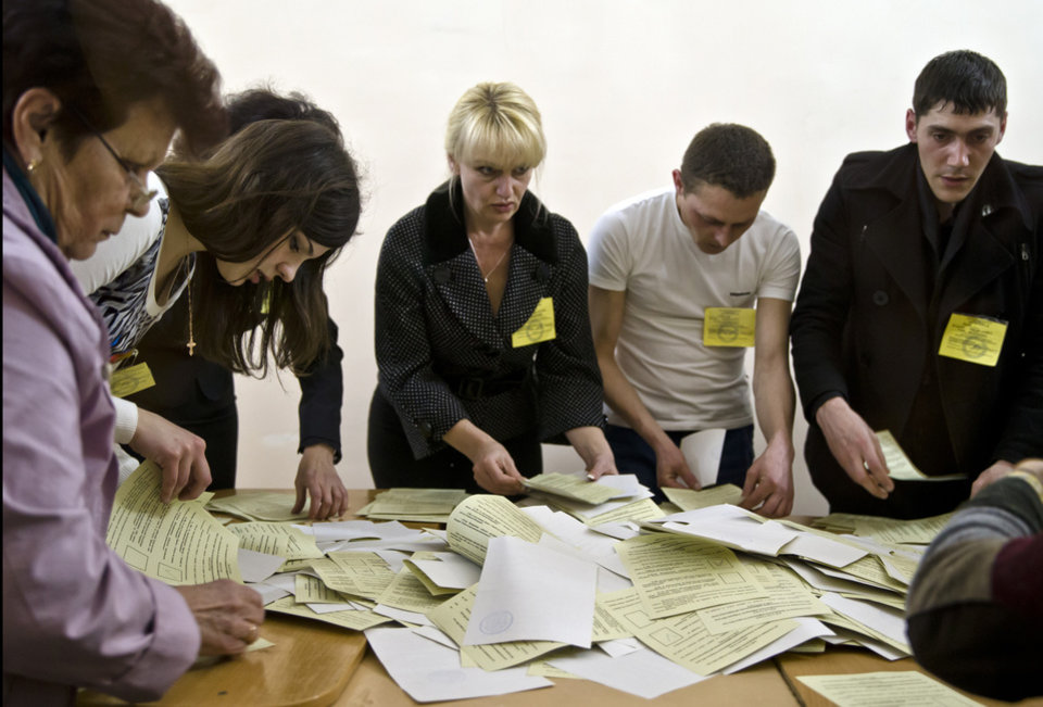 Photo - Referendum officials sort ballots at a polling station in Simferopol, Ukraine, Sunday, March 16, 2014. Polls have closed in Crimea's contentious referendum on seceding from Ukraine and seeking annexation by Russia. The vote, unrecognized both by the Ukrainian government and the West, was held Sunday as Russian flags fluttered in the breeze and retirees grew weepy at the thought of reuniting with Russia. (AP Photo/Vadim Ghirda)