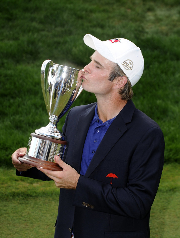 Photo - Kevin Streelman kisses the trophy after winning the Travelers Championship golf tournament in Cromwell, Conn., Sunday, June 22, 2014. Streelman finished his round with seven straight birdies to win the tournament at 15-under par. (AP Photo/Fred Beckham)
