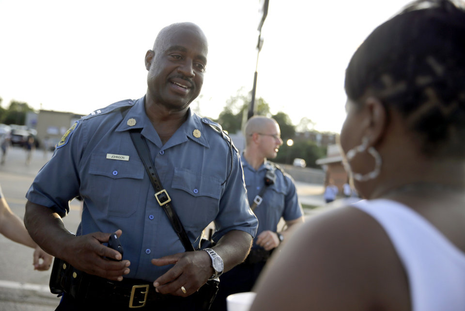 Photo - Missouri Highway Patrol Capt. Ron Johnson meets with residents while walking the streets Tuesday, Aug. 19, 2014, in Ferguson, Mo. Ferguson's leaders urged residents Tuesday to stay home after dark to
