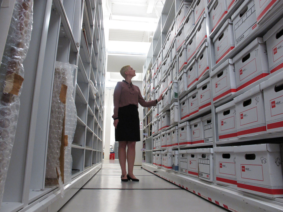 Photo - In this May 8, 2014 photo, University of South Carolina archivist Jessica Crouch looks over 83 boxes of author Pat Conroy's papers at the university's library in Columbia, S.C. The university has obtained all of Conroy's handwritten manuscripts and other papers. (AP Photo/Jeffrey Collins)