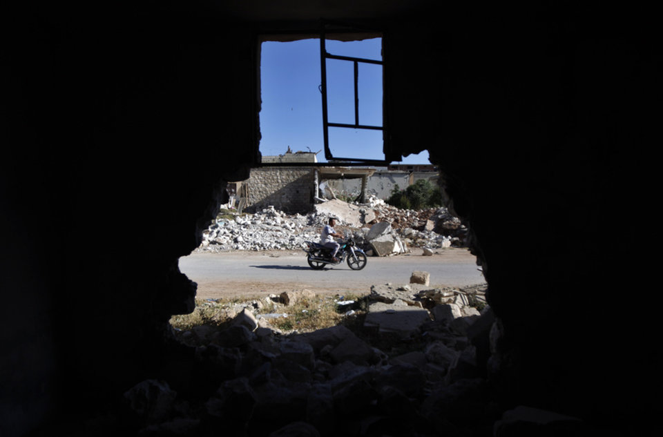 Photo -   FILE - In a Tuesday, June 5, 2012 file photo, a Syrian man rides a motorcycle by the rubble of house that was destroyed during a military operation by the Syrian pro-Assad army in April 2012 , in the town of Taftanaz, 15 kiolmeters east of Idlib, Syria. At dawn on April 3, Syrian forces shelled the town in the first volley of what residents say was a massive assault after a string of large protests calling for the end of the autocratic rule of President Bashar Assad. (AP Photo/Khalil Hamra, File)