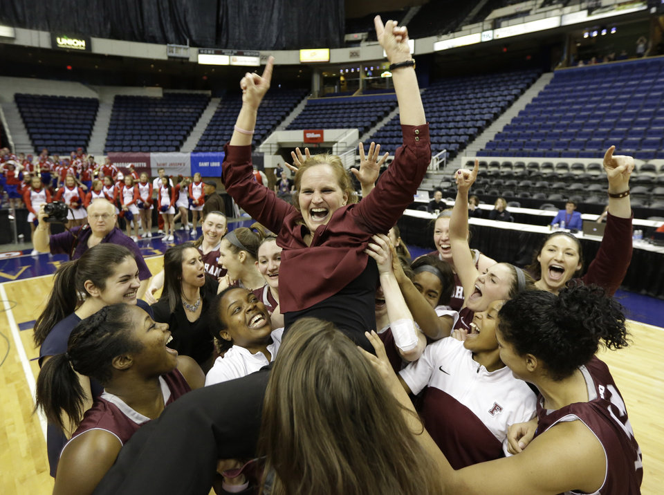Photo - Fordham head coach Stephanie Gaitley is lifted up by her team after they won the A10 Women's basketball championship game in Richmond, Va., Sunday, March 9, 2014. Fordham defeated Dayton 63-51. (AP Photo/Steve Helber)