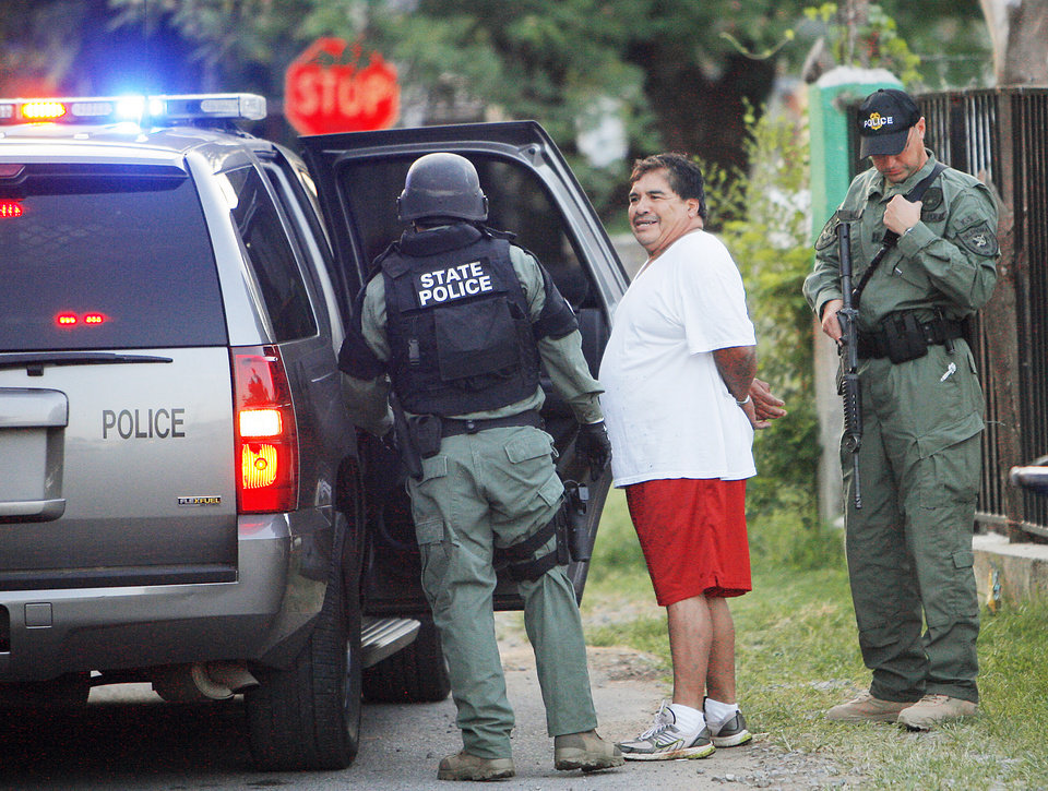 Photo - An Oklahoma Bureau of Narcotics agent takes Estanistao Casas-Presa into custody during a meth raid. Oklahoma Bureau of Narcotics executed a large-scale raid Tuesday morning, July 14, 2009, in Caddo County, launching out of Anadarko,   Photo By David McDaniel, The Oklahoman.