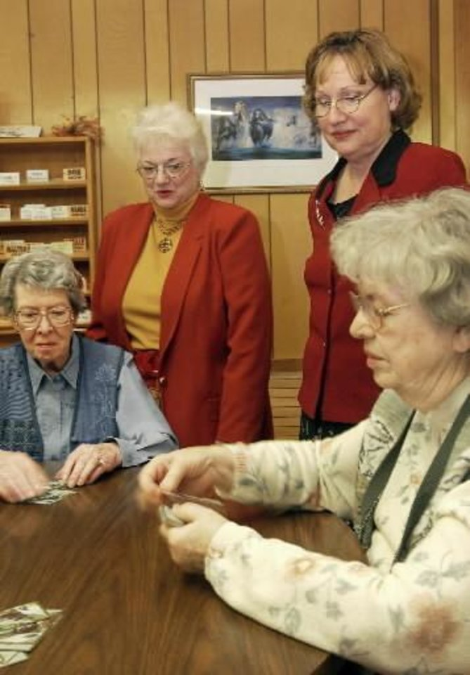 2002 file photo - Marilyn Williams, retiring senior center director, and her replacement  Gail  Deaton watch Virgina Hunkapiller and Alma Bolvin play cards. Staff Photo by David McDaniel.