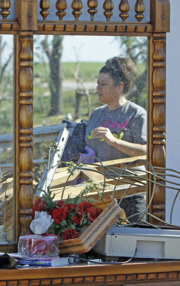 Photo - Kristi McDaniel-Edwards is reflected in the dresser mirror of her grandmother Louise McDaniel's home as residents cleanup following Tuesday's deadly tornado  on Wednesday, May 25, 2011, in Chickasha, Okla.  Louise was with her hospitalized son Ronnie McDaniel in Oklahoma City when the tornado destroyed her home.  Louise McDaniel saw the destruction and recognized her yard from aerial television coverage. Photo by Steve Sisney, The Oklahoman