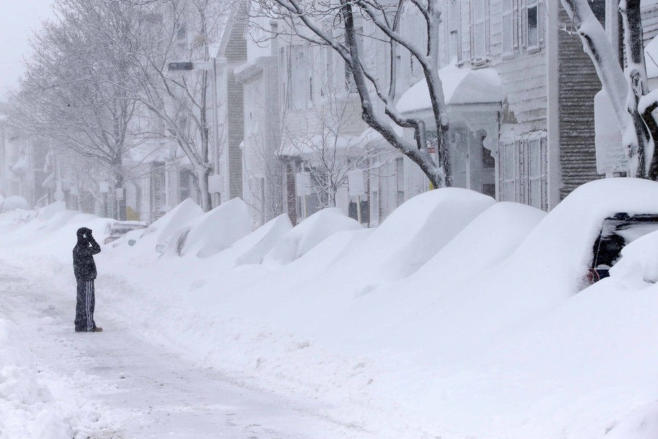 Photo - A man talks on the phone as he looks at a row of cars buried in snow on Third Street in the South Boston neighborhood of Boston Saturday, Feb. 9, 2013. (AP Photo/Gene J. Puskar)