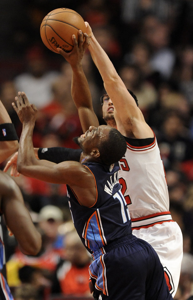 Photo - Charlotte Bobcats' Kemba Walker (15), goes up for a shot against Chicago Bulls' Kirk Hinrich (12), during the first quarter of an NBA basketball game in Chicago, Monday, Nov. 18, 2013. (AP Photo/Paul Beaty)