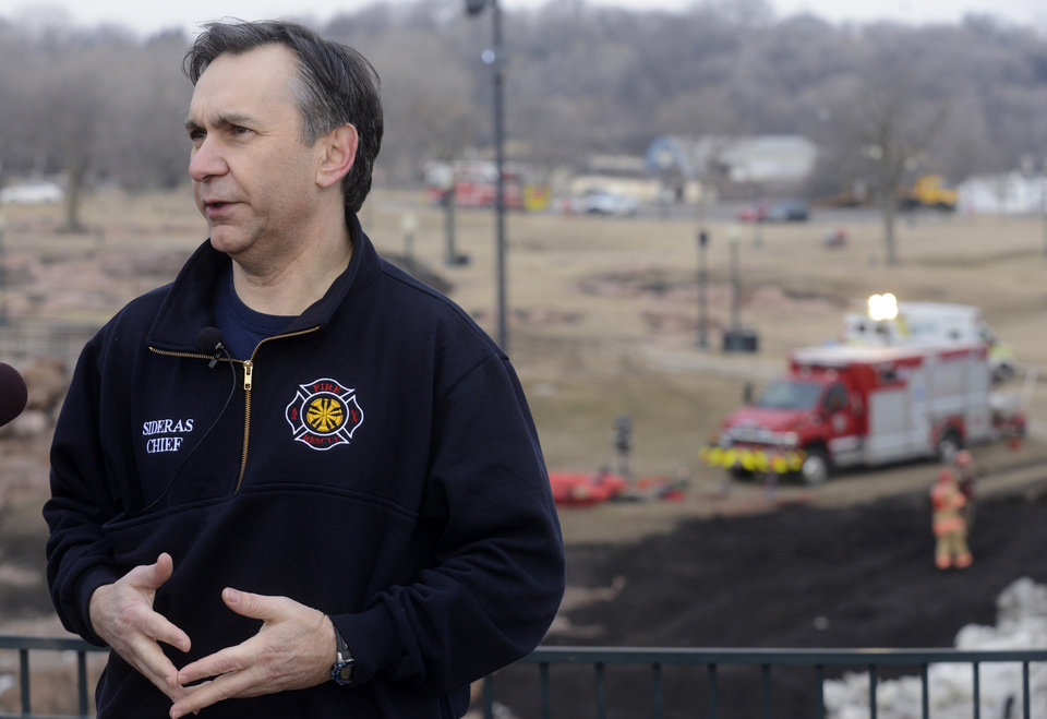 Photo - Sioux Falls Fire Rescue Chief, Jim Sideras briefs the media Friday, March 15, 2013, as crews work to recover the bodies of two adults that went into the Big Sioux River to rescue a 6 year old boy that fell into the water below the falls at Falls Park Thursday evening in Sioux Falls, S.D.  Sioux Falls Fire Chief Jim Sideras said early Friday a woman who a relative of the boy's but not his mother jumped into the water to try to save the boy, and a man jumped in to try to save the woman and child. The boy emerged from the water a short time later downstream at Falls Park, and was not injured.  (AP Photo/Argus Leader, Elisha Page) NO SALES