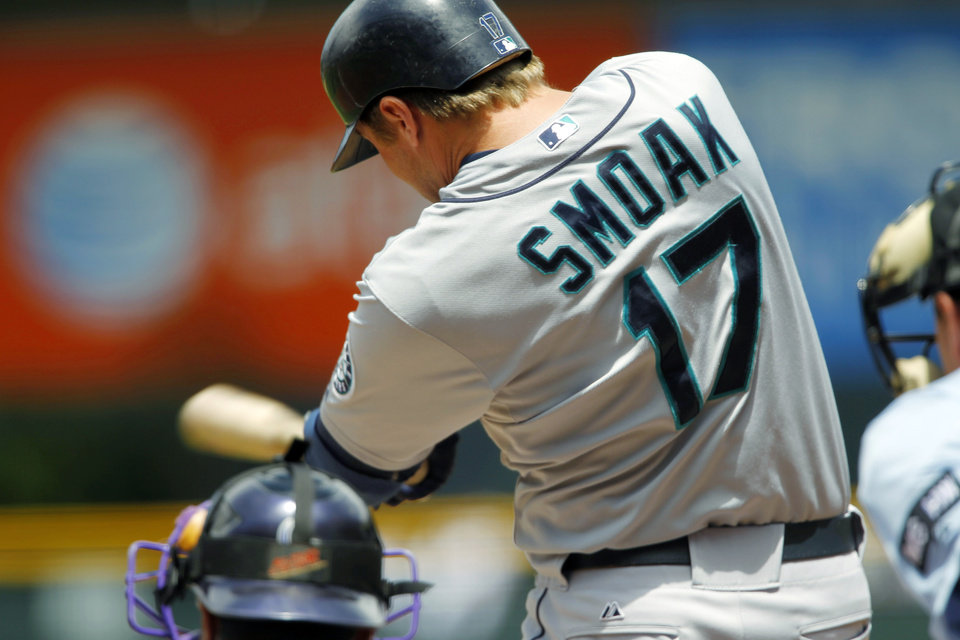 Photo -   Seattle Mariners' Justin Smoak connects for an RBI-single against Colorado Rockies starting pitcher Jeremy Guthrie in the first inning of an interleague baseball game in Denver on Sunday, May 20, 2012. (AP Photo/David Zalubowski)