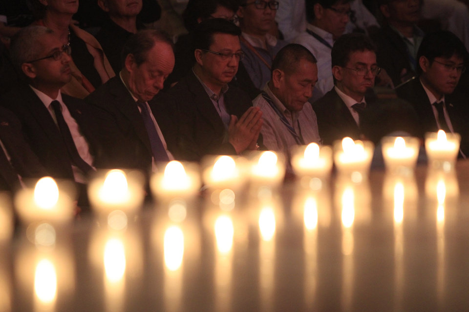 Photo - Malaysian Transport Minister Liow Tiong Lai, third from left, prays beside Malaysia Airlines Group Chief Executive Ahmad Jauhari Yahya, third from right, during a multi-faith prayers for the victims of the downed Malaysia Airlines Flight 17 at Malaysia Airlines Academy in Kelana Jaya, near Kuala Lumpur, Malaysia, Friday, July 25, 2014. A small group of Dutch and Australian investigators walked the sprawling, unsecured site where Malaysian Airlines Flight 17 went down as their governments prepared police detachments they hope can help protect the crash area and help bring the last of the victims home. (AP Photo/Lai Seng Sin)