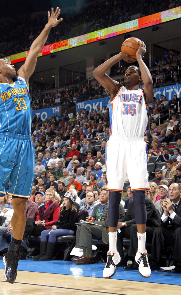 Photo - Oklahoma City's Kevin Durant (35) shoots a 3-pointer over New Orleans' Willie Green (33) during the NBA basketball game between Oklahoma City Thunder and New Orleans Hornet, Wednesday, Feb. 2, 2011 at the Oklahoma City Arena. Photo by Sarah Phipps, The Oklahoman