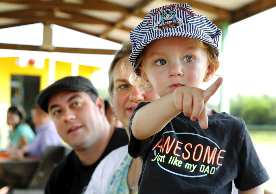 Wearing his Thomas Train engineer cap, Henry Witzke, 2, points to another train on a side track while he rides with his parents, Jeremy and Kristy Witzke of Oklahoma City. His parents said this was Henry's first time to ride a train. Passengers enjoy a 35-minute train trip aboard one of five scheduled Saturday excursion trains that leaves the station at the Oklahoma Railway Museum, 3400 NE Grand Blvd. in Oklahoma City. This photo taken on a train ride on  Saturday,  Aug. 17, 2013.    Photo  by Jim Beckel, The Oklahoman.