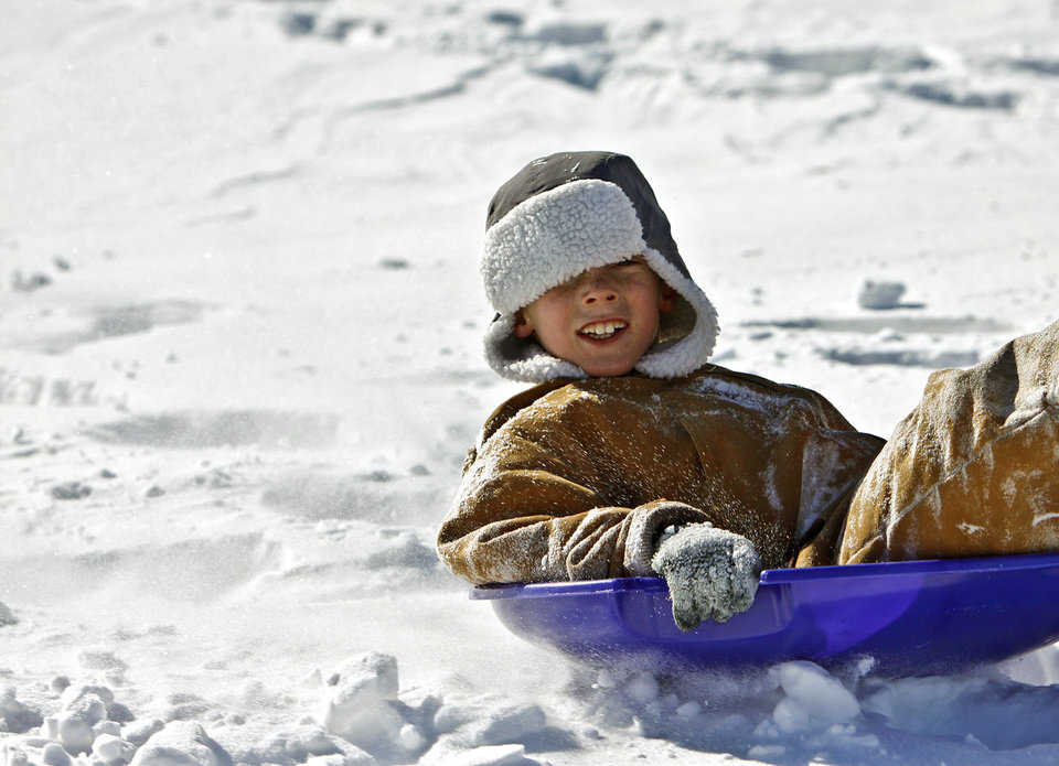 Photo - Christian Grassmann, 8, rides his sled down the hill while enjoying the day out of school at Will Rogers Park on Wednesday, Feb. 2, 2011, Oklahoma City, Okla.   Photo by Chris Landsberger, The Oklahoman