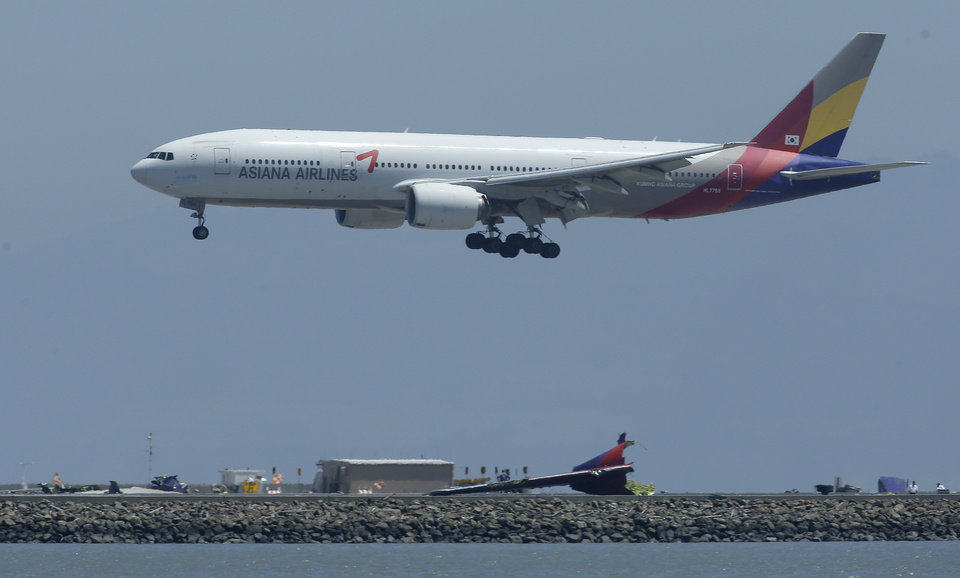 Photo - Tuesday's Asiana Flight 214 comes in for a landing over the wreckage of Saturday's Asiana Flight 214 at San Francisco International Airport in San Francisco, Tuesday, July 9, 2013. Saturday's Asiana Flight 214, crashed upon landing, two of the 307 passengers aboard were killed.,  (AP Photo/Jeff Chiu)