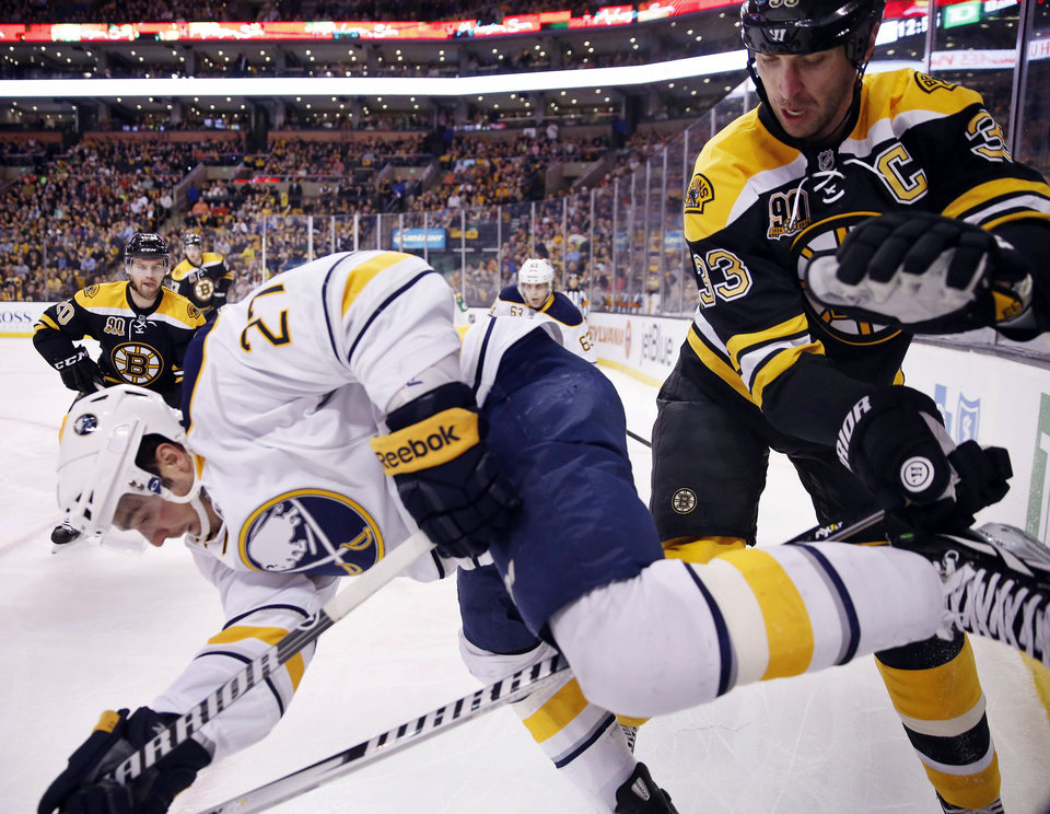 Photo - Boston Bruins' Zdeno Chara (33) and Buffalo Sabres' Matt D'Agostini (27) battle along the boards during the first period of an NHL hockey game in Boston, Saturday, April 12, 2014. (AP Photo/Michael Dwyer)