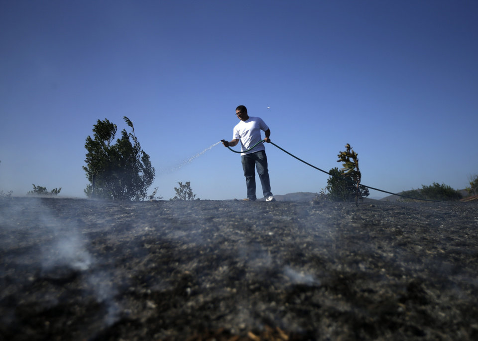 Photo - Anthony Novom waters down smoldering vegetation surrounding his home in the Rancho Santa Fe neighborhood during a wildfire Tuesday, May 13, 2014, in San Diego. Wildfires pushed by gusty winds chewed through canyons parched by California's drought, prompting evacuation orders for more than 20,000 homes on the outskirts of San Diego and another 1,200 homes and businesses in Santa Barbara County 250 miles to the north.  (AP Photo)