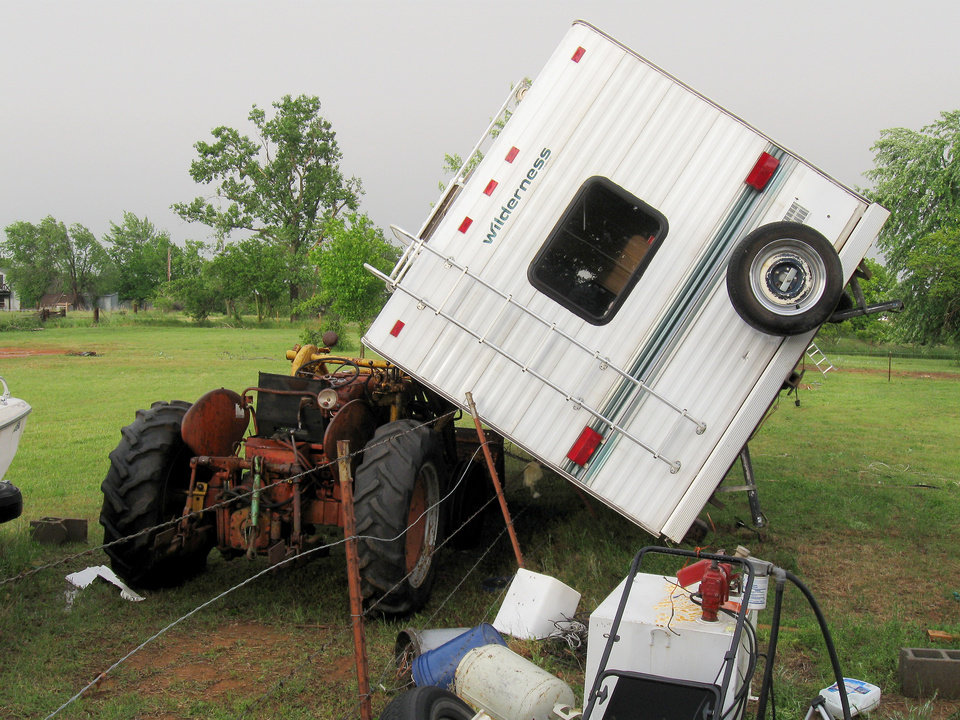 Photo - Left: This camper was blown onto  a tractor near 120th Avenue  and Maguire Road in Norman.  PHOTO BY JAMES TYREE,  THE OKLAHOMAN