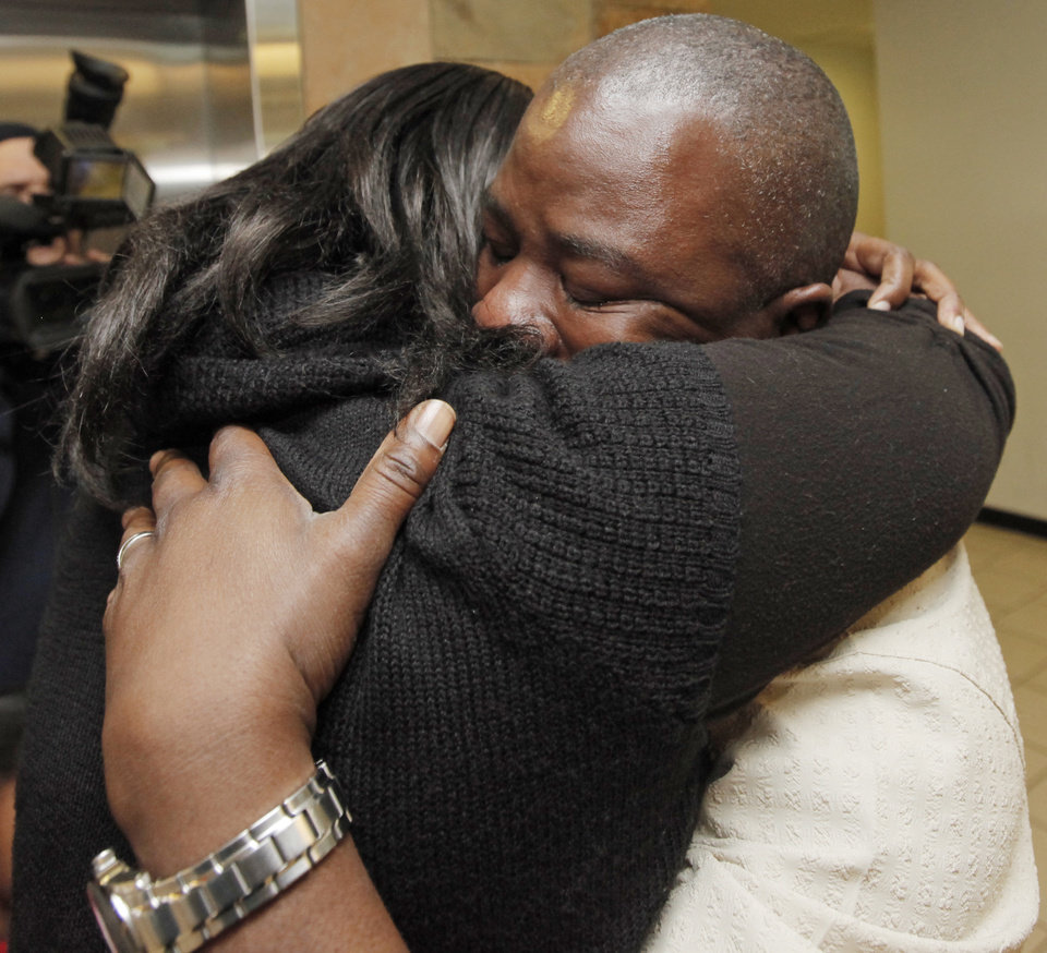 Photo - Humphreys Munai, right, hugs his wife, Judith McCarty-Munai, after arriving at Will Rogers World Airport in Oklahoma City, Thursday, January 14, 2010. Humphreys Munai was returning from Haiti where he was working for World Neighbors when the recent earthquake devastated the country. Photo by Nate Billings, The Oklahoman