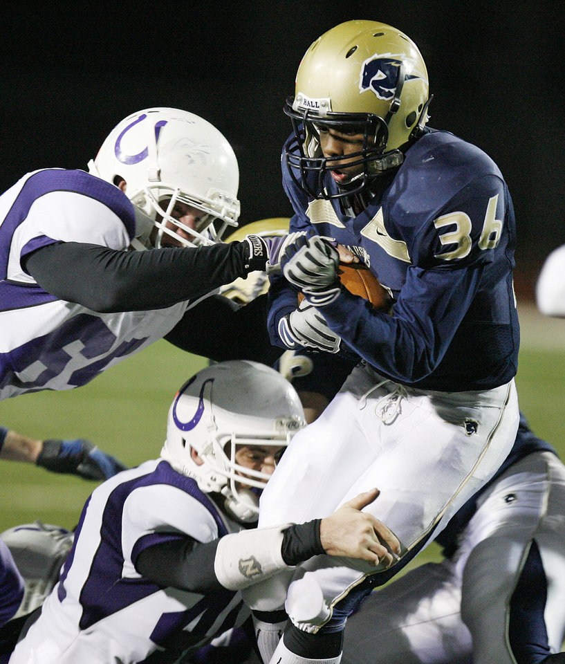 Photo - Heritage Hall's Brent Gaddis (36) is stopped by a pair of Bethany defenders on a carry during the Class 3A high school football semifinal playoff  game between Heritage Hall and Bethany at Putnam City High School in Oklahoma City, Saturday, December 4, 2010. Photo by Nate Billings, The Oklahoman