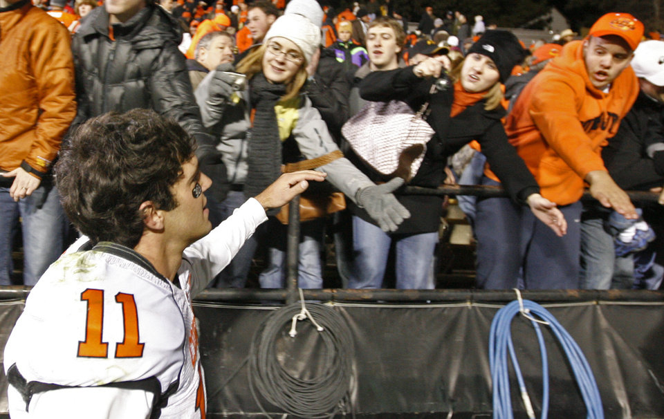 Photo - OSU quarterback Zac Robinson (11) greets fans after the college football game between Oklahoma State University and University of Colorado at Folsom Field in Boulder, Colo., Saturday, Nov. 15, 2008. OSU won, 30-17. BY NATE BILLINGS, THE OKLAHOMAN