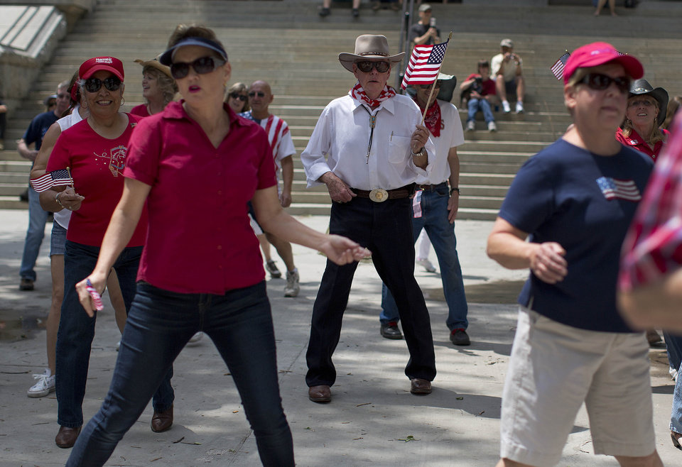 Edward Blades, center, dances in a flash mob line dance with other Prescott city residents outside the Yavapai County Courthouse, Thursday, July 4, 2013 in Prescott, Ariz. After 19 Granite Mountain Hotshot firefighters were killed Sunday near Yarnell, Ariz., emotional whiplash has become a matter of course here as residents try to move on and enjoy the biggest tourism week of the year, while also mourning the men who were the town's pride. (AP Photo/Julie Jacobson)