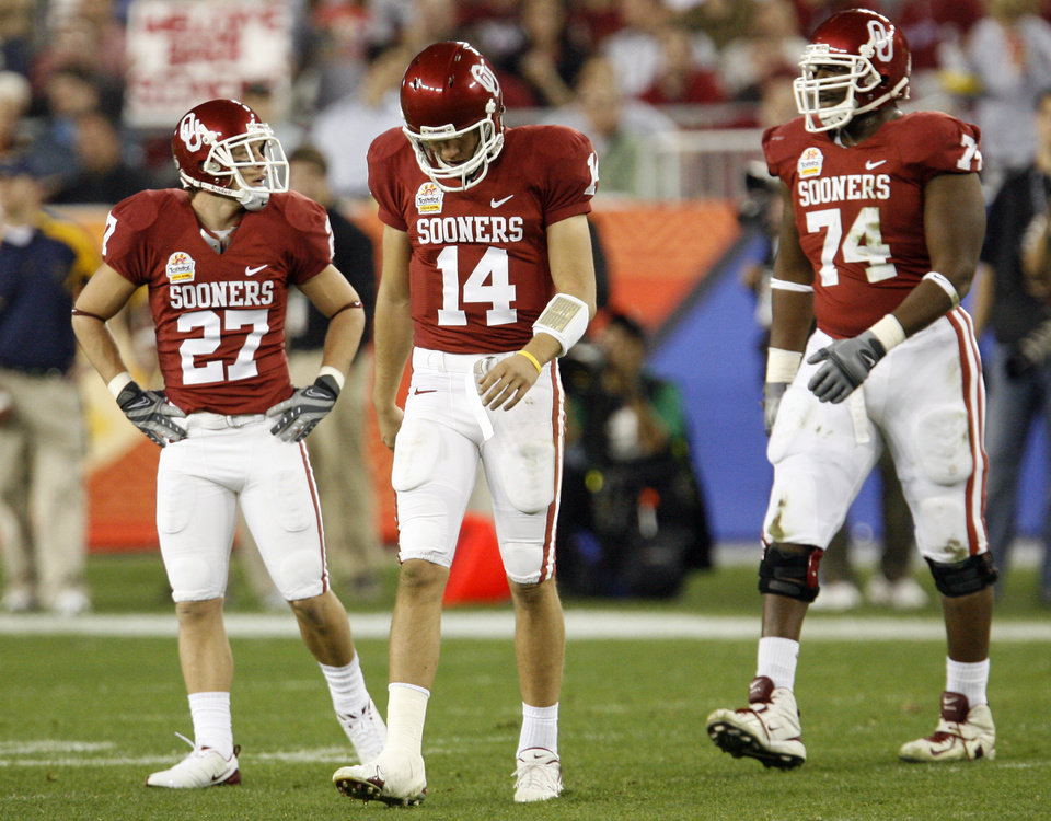 Photo - Oklahoma's Garrett Bothun (27), Sam Bradford (14) and Brian Simmons (74) walk off the field after being stopped by West Virginia during the first half of the Fiesta Bowl college football game between the University of Oklahoma Sooners (OU) and the West Virginia University Mountaineers (WVU) at The University of Phoenix Stadium on Wednesday, Jan. 2, 2008, in Glendale, Ariz. 