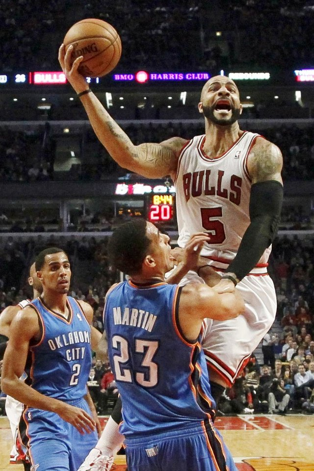 Chicago Bulls forward Carlos Boozer (5) shoots over Oklahoma City Thunder guard Kevin Martin (23) as Thabo Sefolosha (2) watches during the first half of an NBA basketball game, Thursday, Nov. 8, 2012, in Chicago. (AP Photo/Charles Rex Arbogast)