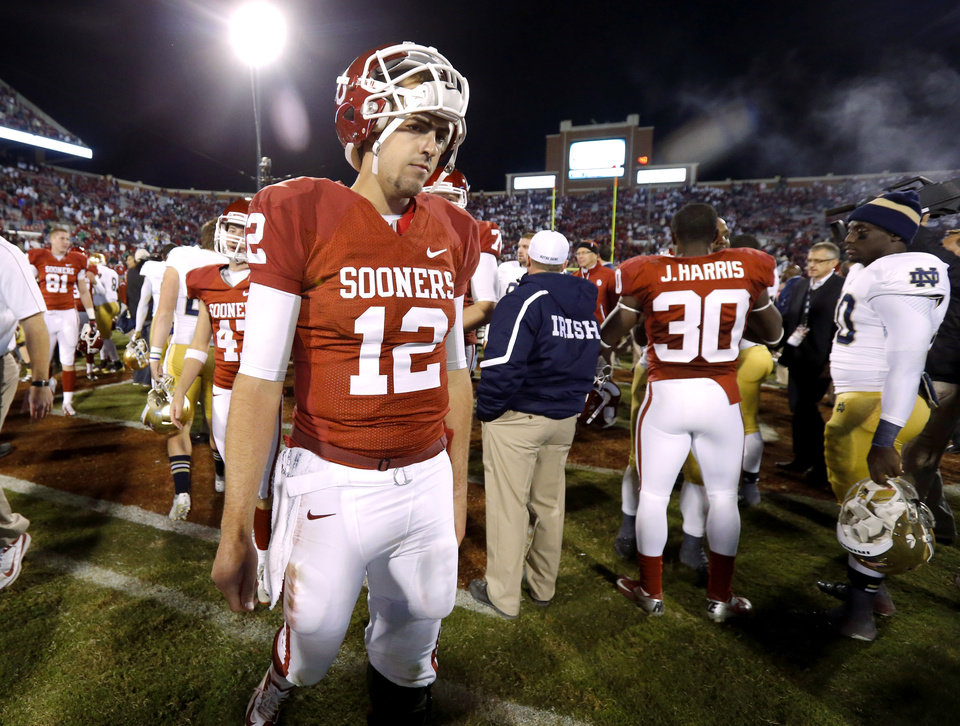 Photo - OU's Landry Jones (12) walks off the field after the college football game between the University of Oklahoma Sooners (OU) and the Notre Dame Fighting Irish at Gaylord Family-Oklahoma Memorial Stadium in Norman, Okla., Saturday, Oct. 27, 2012. Oklahoma lost 30-13. Photo by Bryan Terry, The Oklahoman