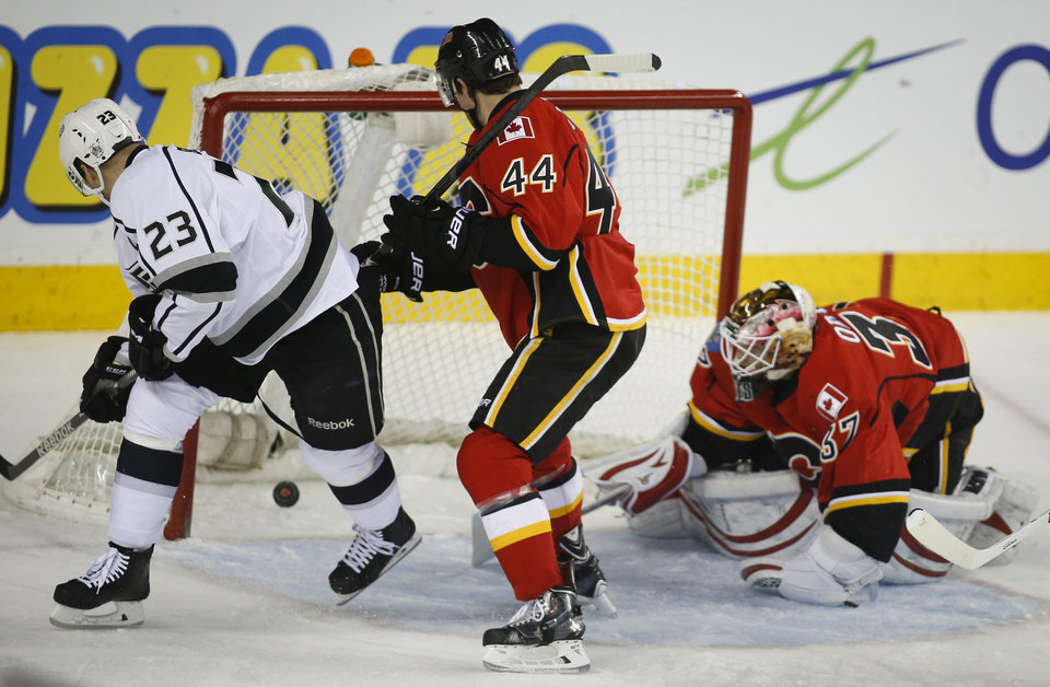 Photo - Los Angeles Kings' Dustin Brown, left, scores on Calgary Flames goalie Joni Ortio, right, from Finland, as Flames' Chris Butler watches during the first period of an NHL hockey game Thursday, Feb. 27, 2014, in Calgary, Alberta. (AP Photo/The Canadian Press, Jeff McIntosh)