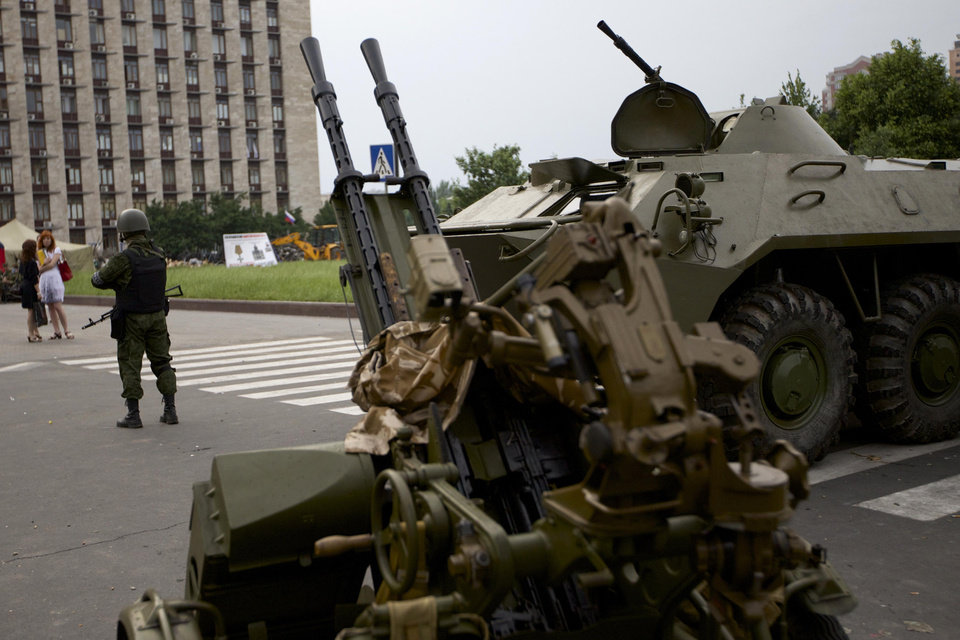 Photo - A Pro-Russian militia member guards next to an APC and anti-aircraft gun, outside the administrational building in Donetsk, Ukraine, on Thursday, May 29, 2014. Pro-Russian militia in eastern Ukraine shot down a government military helicopter Thursday amid heavy fighting around Slovyansk, killing 14 soldiers including a general. (AP Photo/Ivan Sekretarev)
