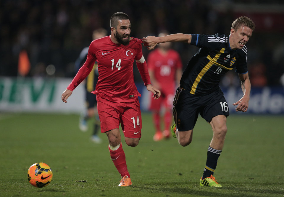 Photo - Turkey's Arda Turan, left, vies with Sweden's Pontus Wernbloom during their International Friendly soccer match at 19 Mayis Stadium in Ankara, Turkey, Wednesday, March 5, 2014.(AP Photo)