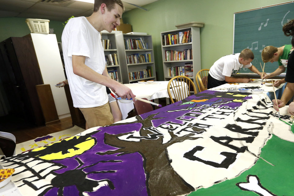 Bishop McGuinness senior Connor Ferguson works on carnival signs as part of a senior class community service project at The Sanctuary women�s development center, 2133 SW 11 in Oklahoma City.  Photo by SARAH PHIPPS, The Oklahoman