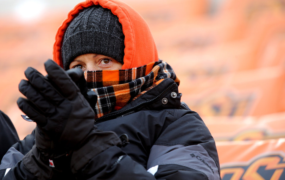 Photo - An Oklahoma State fan braves the cold during the Bedlam college football game between the Oklahoma State University Cowboys (OSU) and the University of Oklahoma Sooners (OU) at Boone Pickens Stadium in Stillwater, Okla., Saturday, Dec. 7, 2013. Photo by Chris Landsberger, The Oklahoman