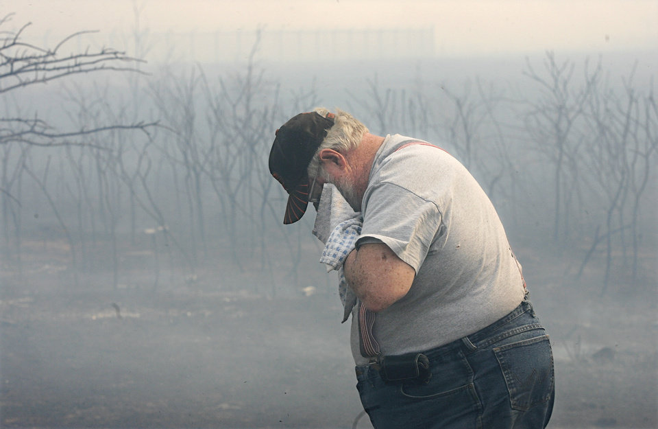 Photo - Milburn Brewer covers his mouth and nose with a wet rag after he doused flames  in this field behind the Windsong Addition in Midwest City,  Thursday, April 9, 2009. This is where the fire began that eventually claimed dozens of homes as it moved to the north and east of this location. Brewer lives in the Windsong Addition and his home was not damaged by the flames.  Photo by Jim Beckel, The Oklahoman