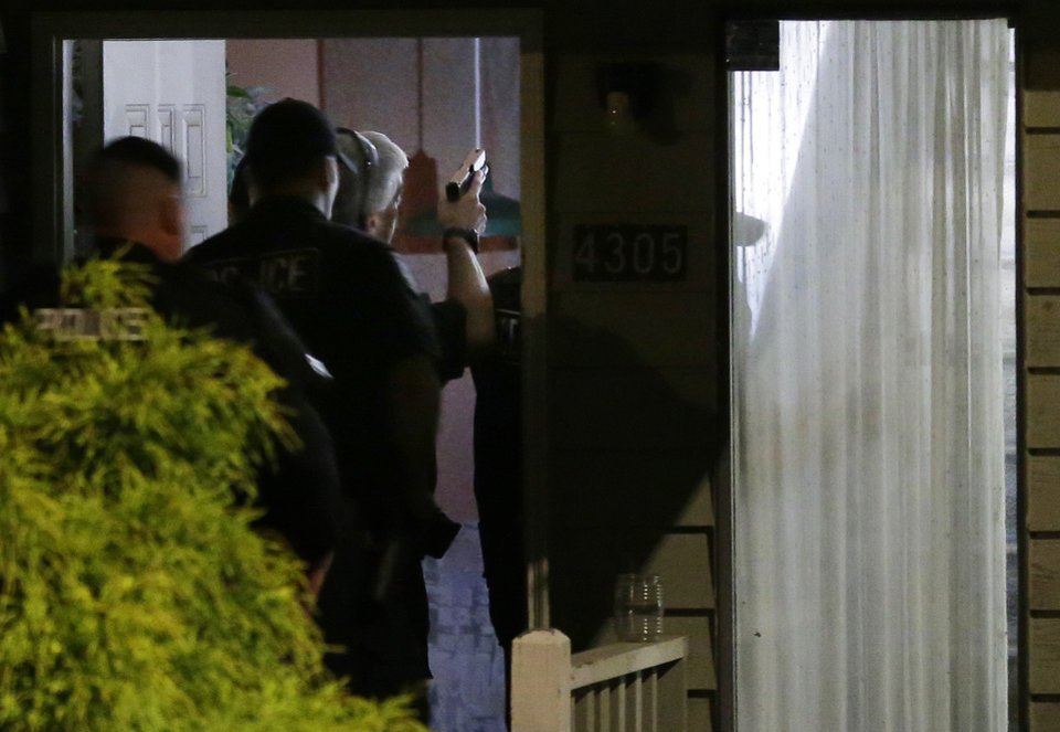 Photo - With guns drawn, police officers enter a home believed to be tied to Aaron R. Ybarra, who was arrested Thursday, June 5, 2014 following a shooting at Seattle Pacific University in Seattle. (AP Photo/Ted S. Warren)