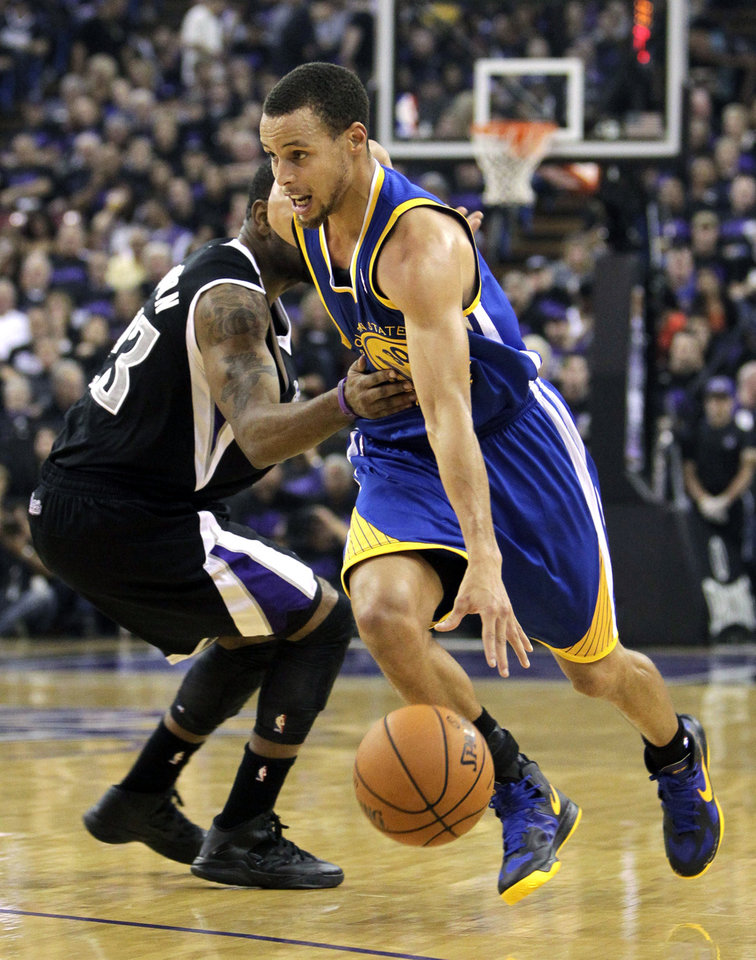 Golden State Warriors guard Stephen Curry, right, drives past Sacramento Kings guard Marcus Thornton during the first half of an NBA basketball game in Sacramento, Calif., Monday, Nov. 5, 2012. (AP Photo/Rich Pedroncelli)