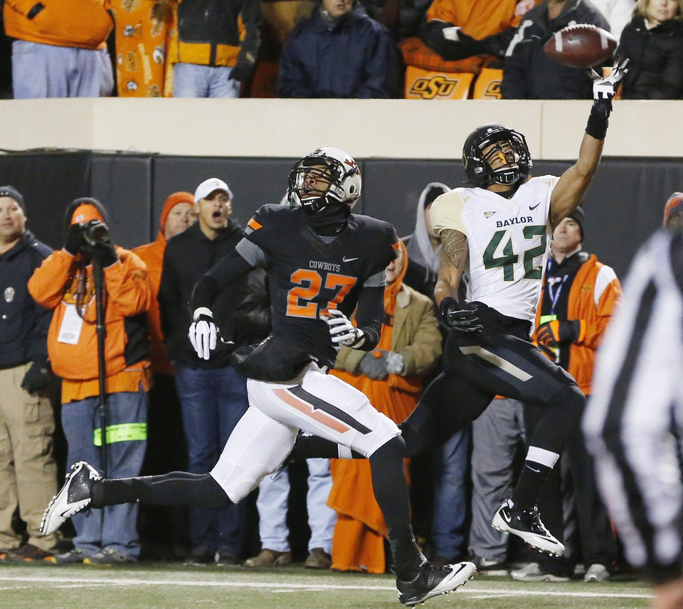 Photo - Baylor receiver Levi Norwood (42) can't make the catch on a pass in front of Oklahoma State safety Lyndell Johnson (27) in the second quarter of an NCAA college football game in Stillwater, Okla., Saturday, Nov. 23, 2013. (AP Photo/Sue Ogrocki)