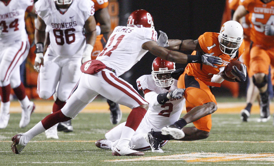 Photo - OU's Lendy Holmes (11) and Brian Jackson (2) bring down OSU's Dez Bryant during the first half of the college football game between the University of Oklahoma Sooners (OU) and Oklahoma State University Cowboys (OSU) at Boone Pickens Stadium on Saturday, Nov. 29, 2008, in Stillwater, Okla. STAFF PHOTO BY BRYAN TERRY