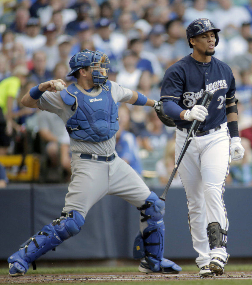 Photo - Milwaukee Brewers center fielder Carlos Gomez, right, reacts to striking out against the Los Angeles Dodgers during the first inning of a baseball game Saturday, Aug. 9, 2014, in Milwaukee. (AP Photo/Darren Hauck)