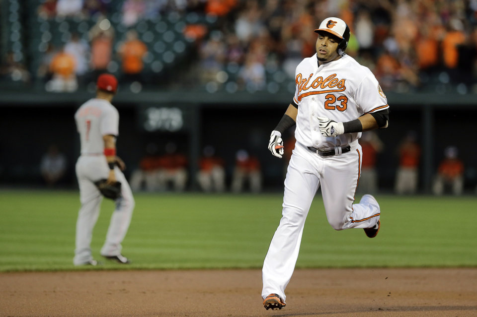 Photo - Baltimore Orioles' Nelson Cruz rounds the bases after hitting a two-run home run in the first inning of an interleague baseball game against the Cincinnati Reds, Thursday, Sept. 4, 2014, in Baltimore. (AP Photo/Patrick Semansky)