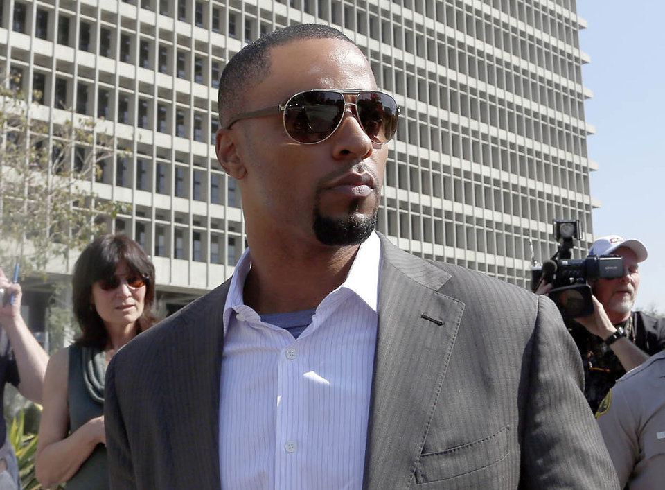 Photo - FILE - In this Feb. 14, 2014, file photo, former NFL safety Darren Sharper leaves a courthouse in Los Angeles. Former NFL All-Pro safety Darren Sharper returns to court Thursday March 13, 2014 for a hearing that will determine whether he's released on bail amid new charges that he drugged and sexually assaulted two women last year in Arizona. (AP Photo/Nick Ut )