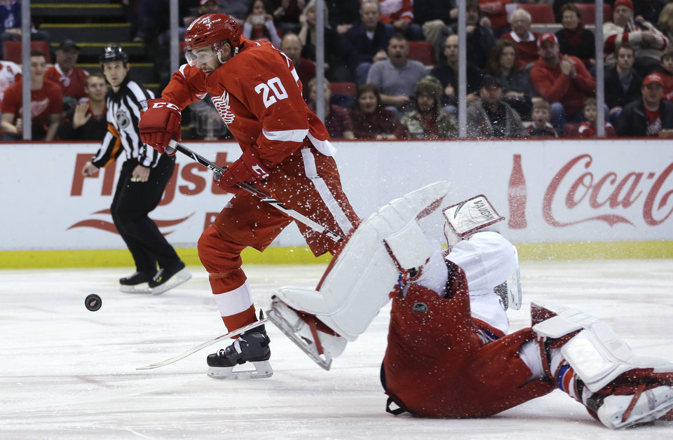 Photo - Detroit Red Wings left wing Drew Miller (20) chases the puck as Washington Capitals goalie Michal Neuvirth, of the Czech Republic,stumbles during the second period of an NHL hockey game in Detroit, Friday, Jan. 31, 2014. (AP Photo/Carlos Osorio)