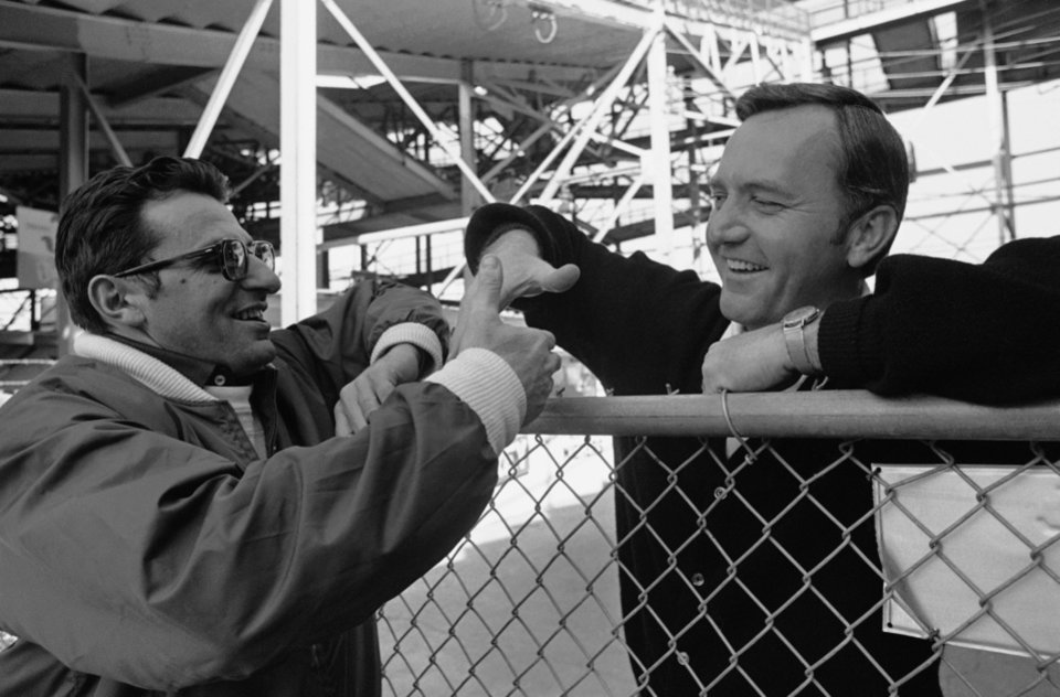 Photo - Penn State coach Joe Paterno (left) reaches across a fence to shake hands with opposing coach Chuck Fairbanks of Oklahoma as the two crossed paths at the practice field in New Orleans on Wednesday, Dec. 27, 1972. The two will meet again in the Sugar Bowl on December 31. (AP Photo)