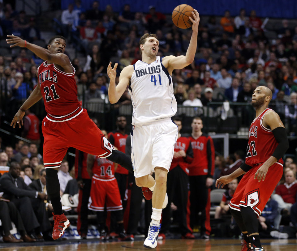 Photo - Dallas Mavericks forward Dirk Nowitzki (41), of Germany, grabs a pass as Chicago Bulls guard Jimmy Butler (21) and forward/center Taj Gibson (22) defend during the second half of an NBA basketball game on Friday, Feb. 28, 2014, in Dallas. Chicago won 100-91. (AP Photo/John F. Rhodes)