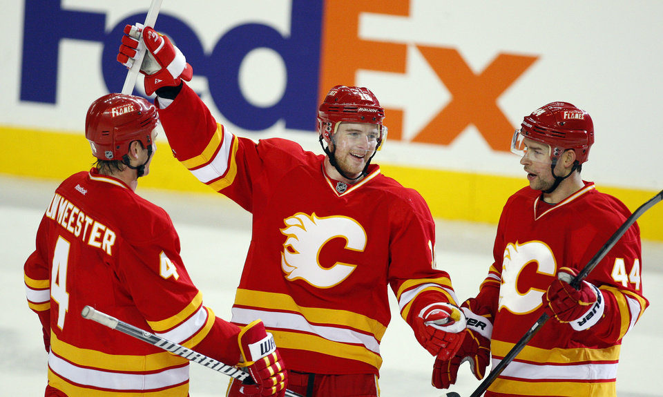 Calgary Flames' Matt Stajan, center, celebrate his second goal with teammates Jay Bouwmeester, left, and Chris Butler during the third period of an NHL hockey game against the Minnesota Wild in Calgary, Alberta, Saturday, Feb. 23, 2013. (AP Photo/The Canadian Press, Jeff McIntosh)