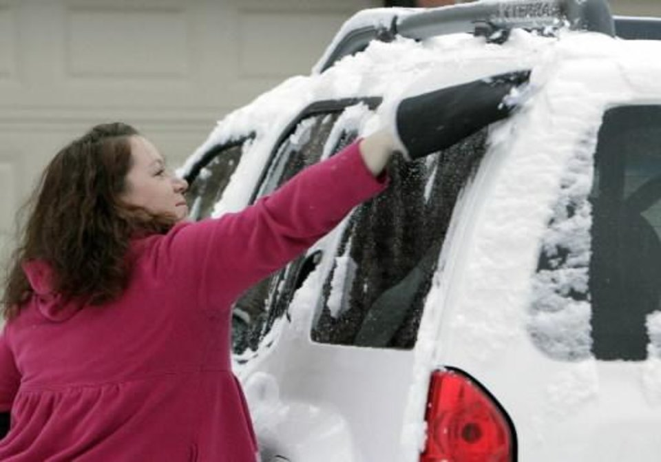 Photo - Edmond resident Kim White uses a mitt to clear her car of about an inch of snow that fell overnight in Edmond, OK, Monday, Feb. 13, 2012. By Paul Hellstern