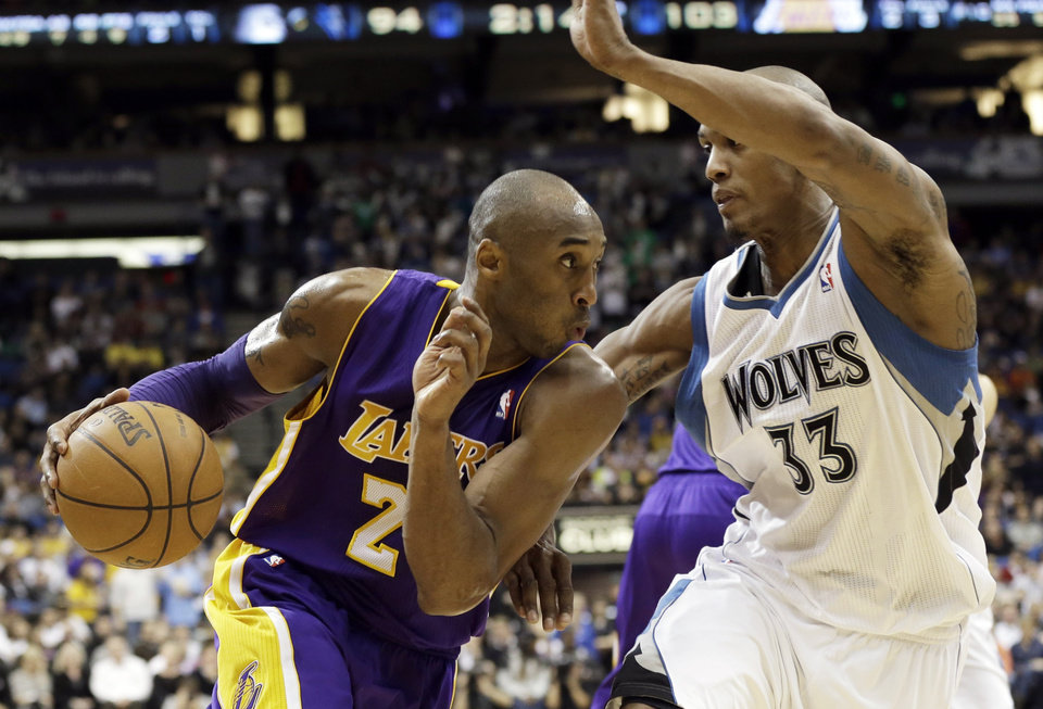 Photo - Los Angeles Lakers' Kobe Bryant, left, drives the basket on Minnesota Timberwolves' Dante Cunningham in the third quarter of an NBA basketball game Friday, Feb. 1, 2013 in Minneapolis.  Bryant scored 17 points and had 12 rebounds along with Pau Gasol as the Lakers won 111-100. (AP Photo/Jim Mone)