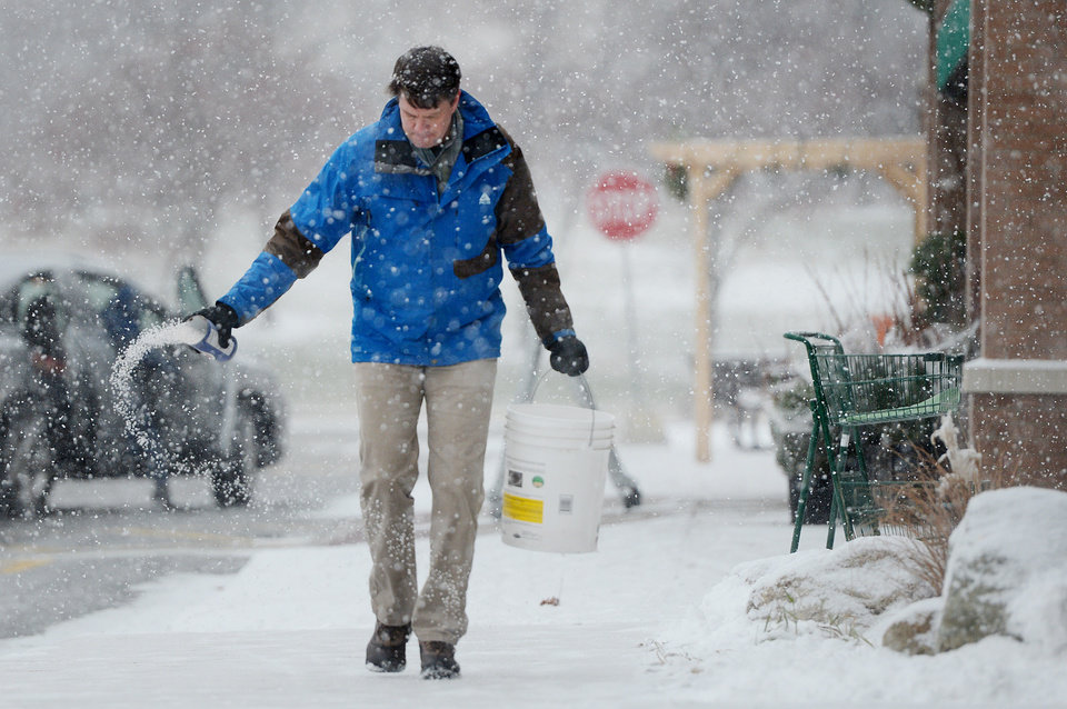 Photo - REI Assistant Store Manager Noel Seeburg salts the sidewalk after shoveling in front of the store located in the Cranbrook Village Shopping Center in Ann Arbor, Mich. on Wednesday, Dec. 26, 2012.  (AP Photo/AnnAbor.Com, Melanie Maxwell)