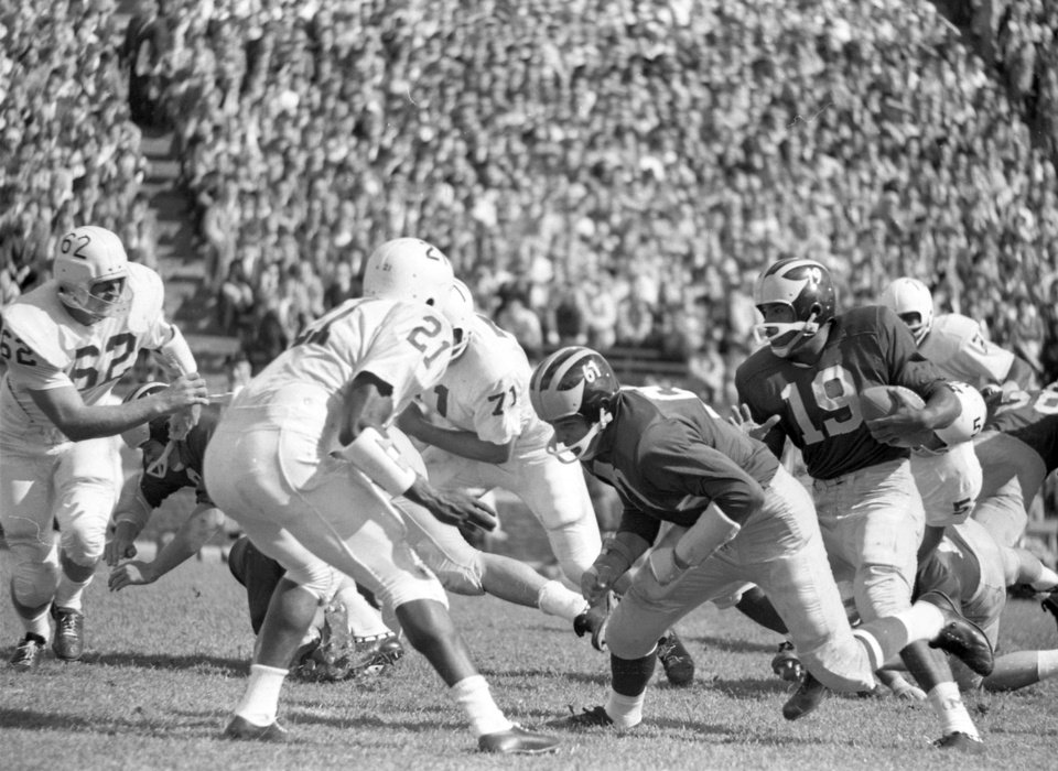 In this photo taken Sept. 29, 1962 and released by the University of Michigan, Michigan's Dave Raimey (19) follows a block by John Marcum (61) during an NCAA college football game in Ann Arbor, Mich. Games between Nebraska and Michigan have been few and far between. Now that both are members of the Big Ten's Legends Division, they'll play annually.(AP Photo/University of Michigan)image/jpeg