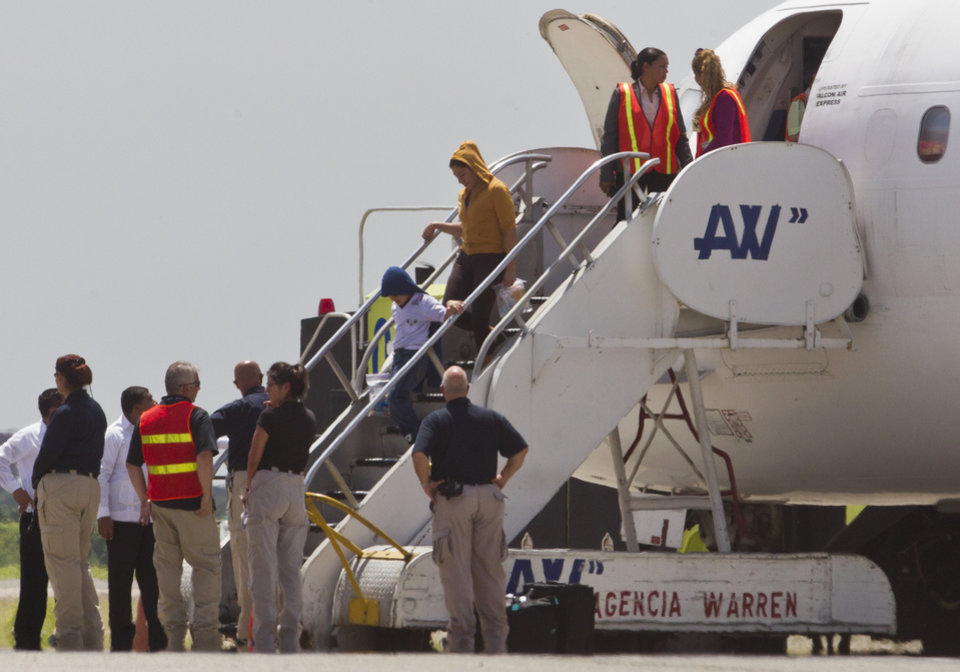 Photo - Immigration and Custom officials standby as a woman and child, who were deported from the United States, deplane at the San Pedro Sula airport, in Honduras, Friday, July 18, 2014. (AP Photo/Esteban Felix)